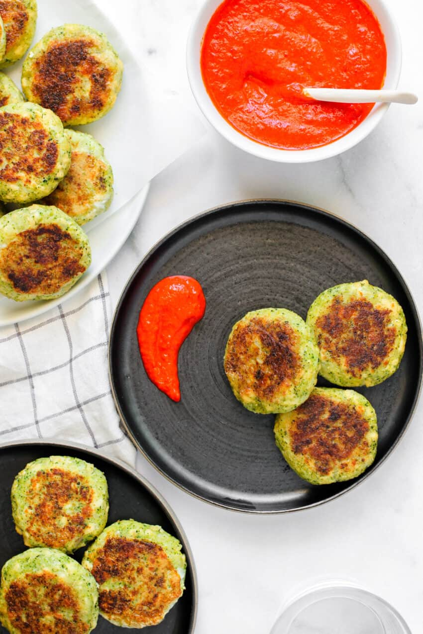 three broccoli and tofu patties on a black plate with red pepper chutney