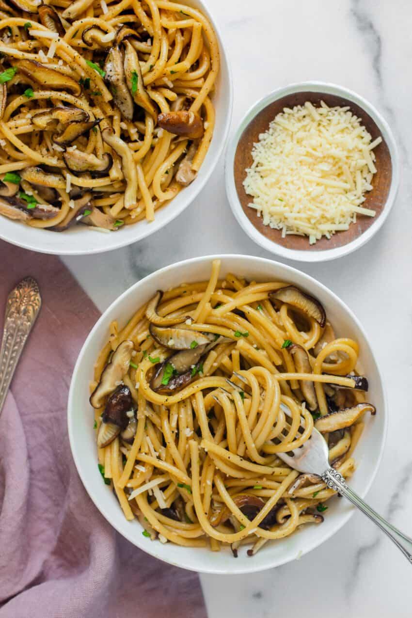 mushroom spaghetti in 2 white bowls