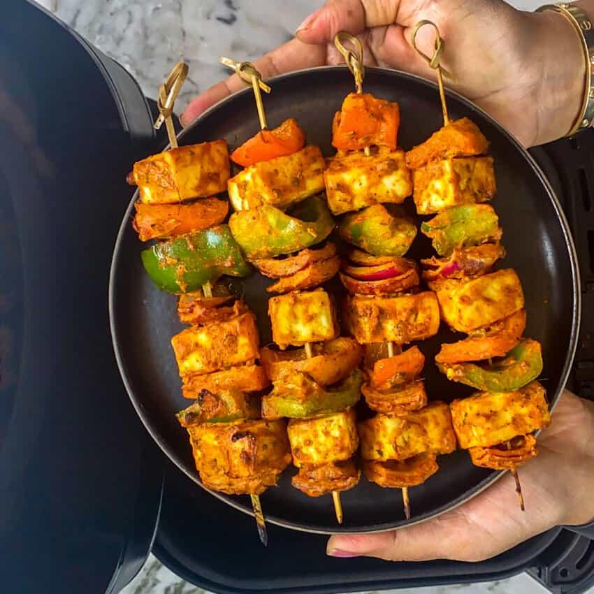 air fried paneer tikka skewers in a black plate