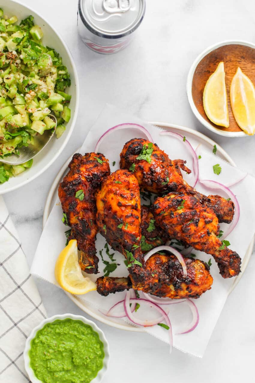 tandoori chicken with lemon wedges and cucumber salad
