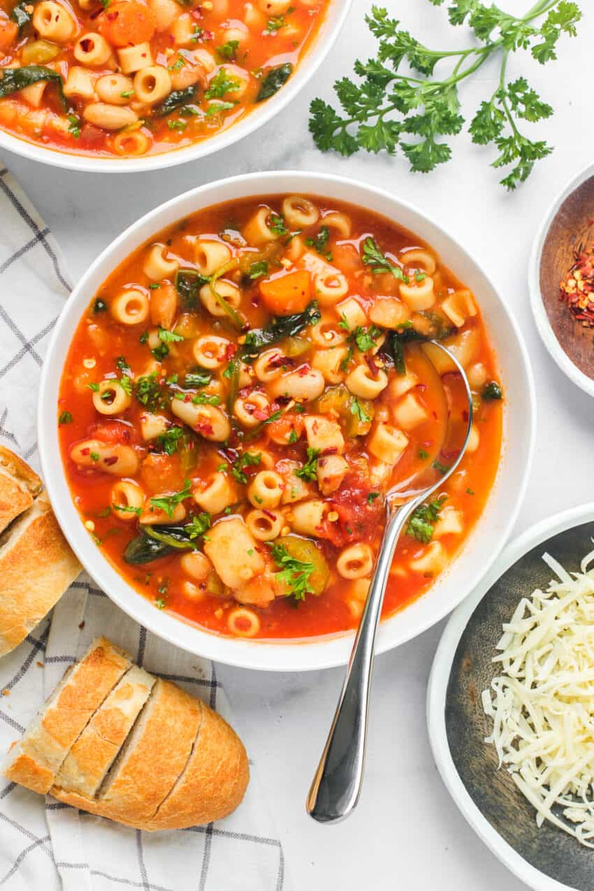 pasta e fagioli soup served in white bowls with baguette
