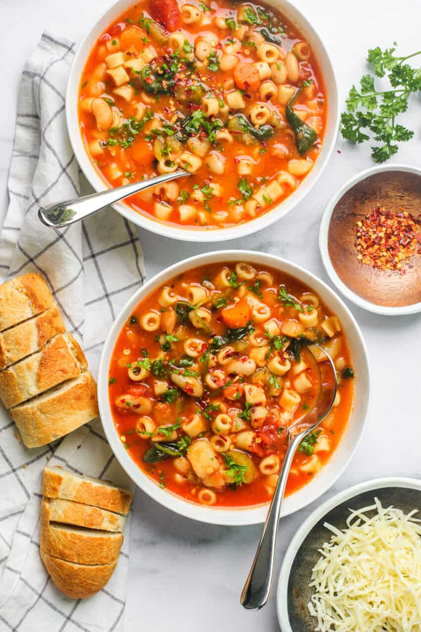 two white bowls with pasta fagioli soup in them