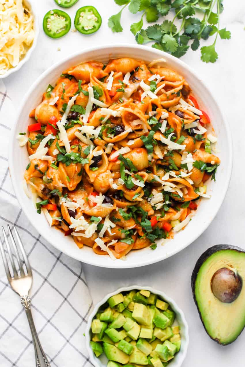Taco pasta served in a white bowl topped with cilantro and cheese