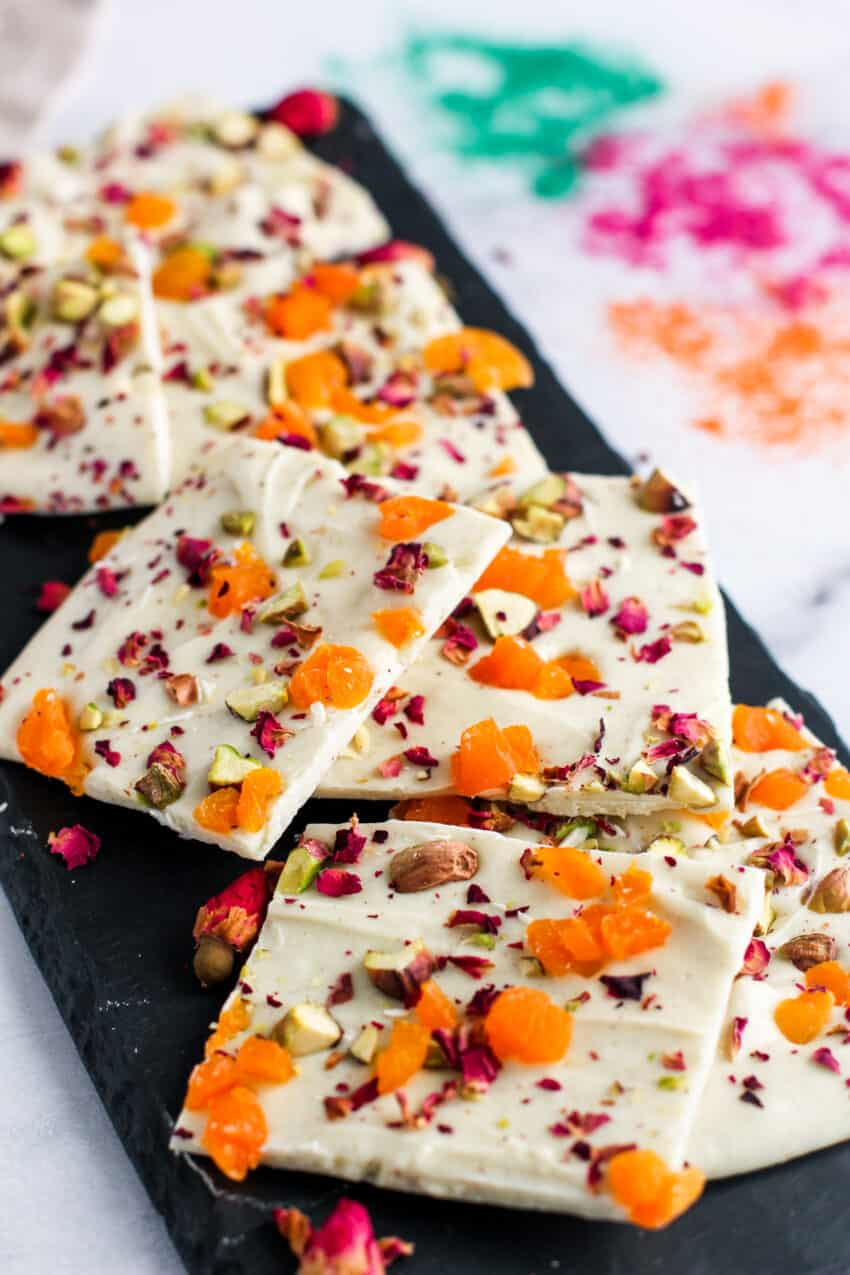 chocolate bark with pistachios, apricots and rose petals on a black platter