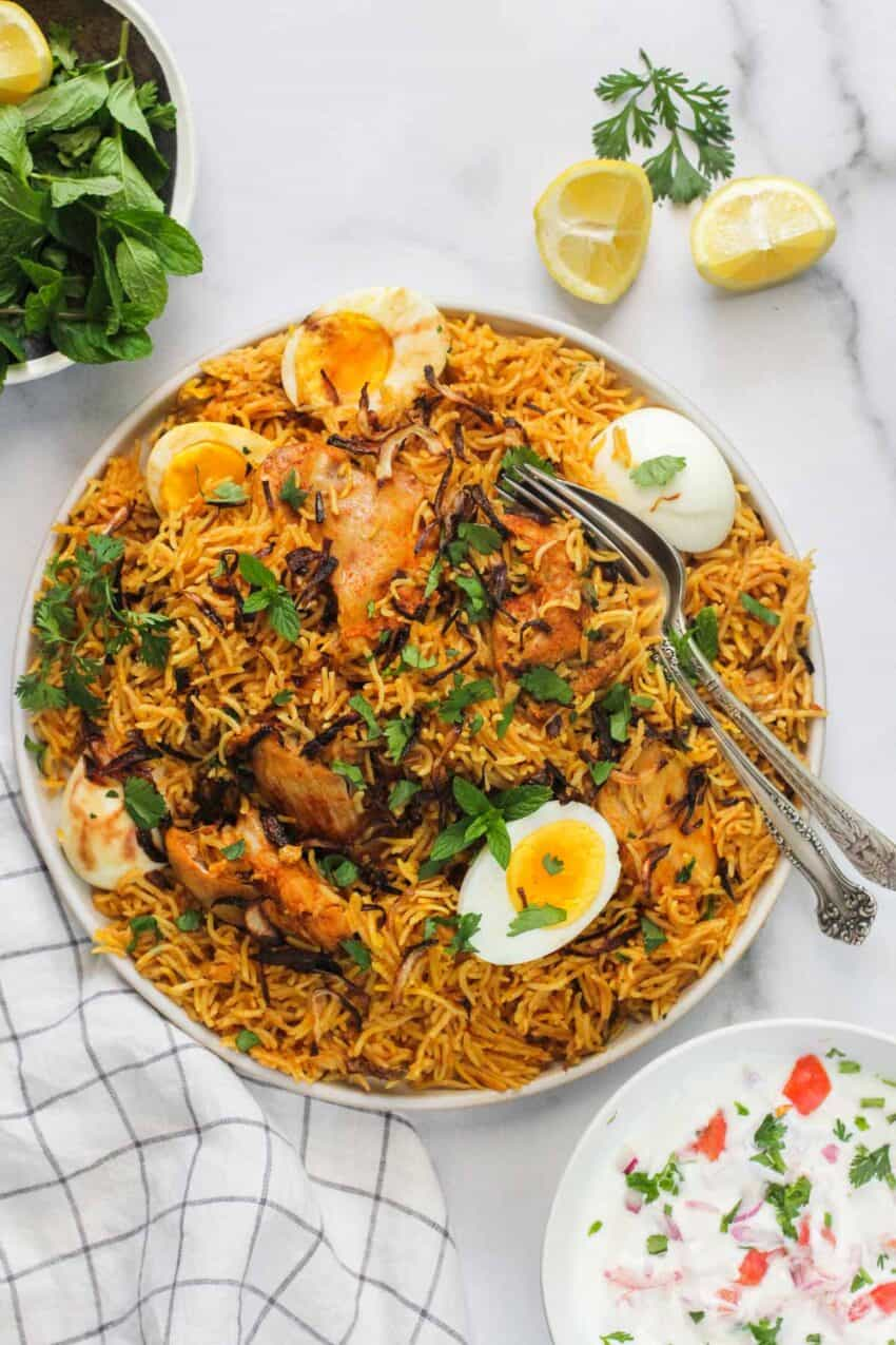 chicken biryani in a platter with hard boiled eggs on top