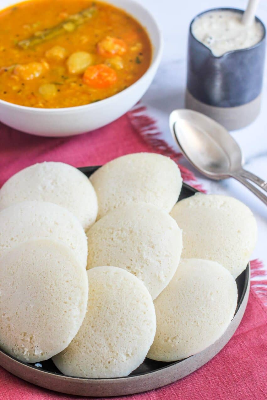 steamed rice cakes next to a bowl of sambar and coconut chutney