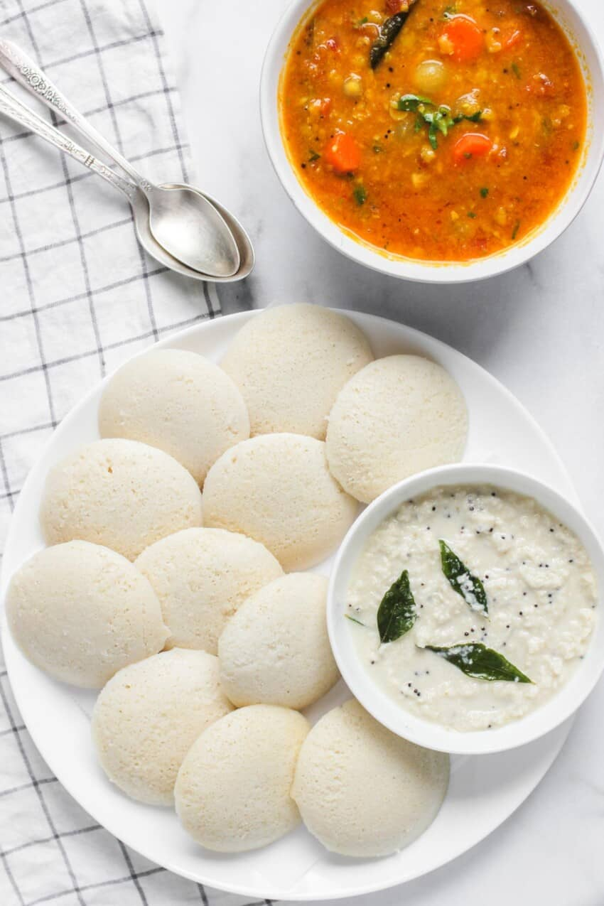 idli in a white platter with coconut chutney in a bowl