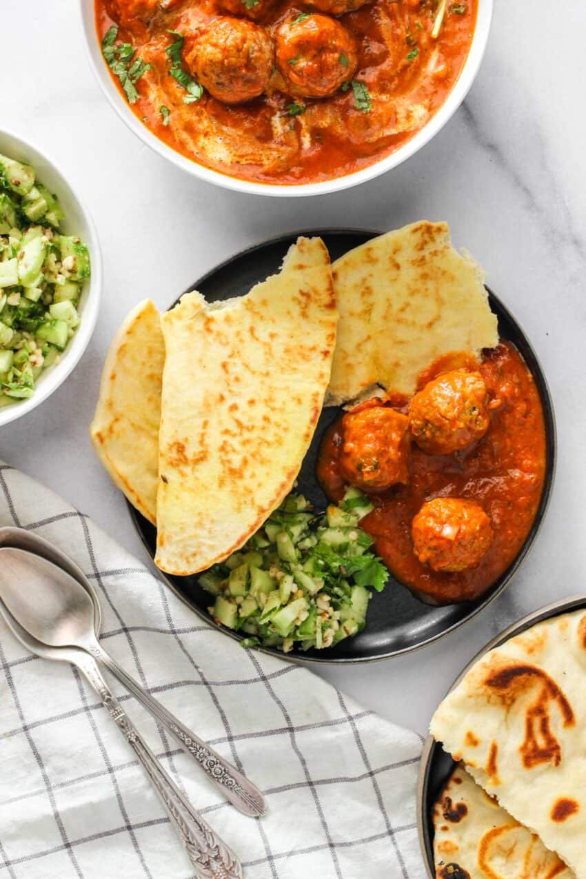 kofta curry served with naan and cucumber salad