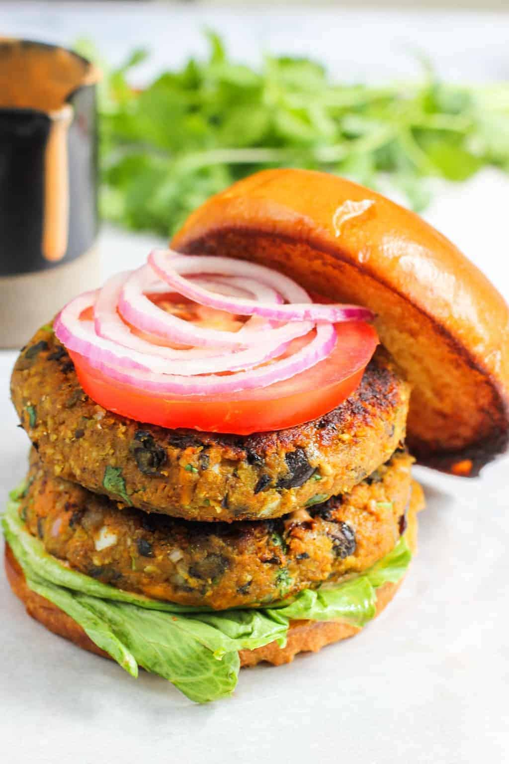 stacked burger patties on buns with lettuce, tomato and onion
