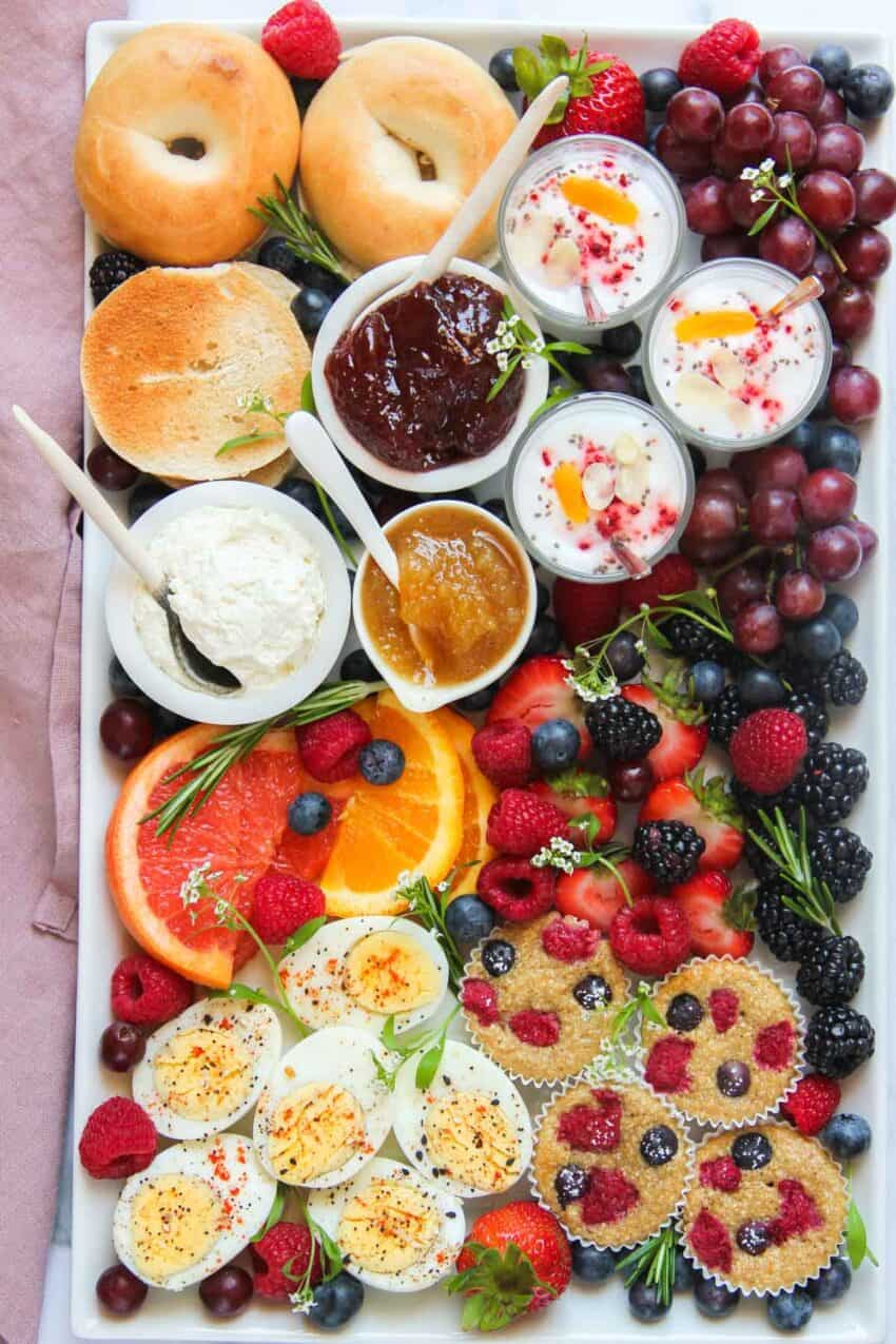 Breakfast Charcuterie Board with bagels, spreads, yogurt parfaits, mini muffins, eggs and fruits