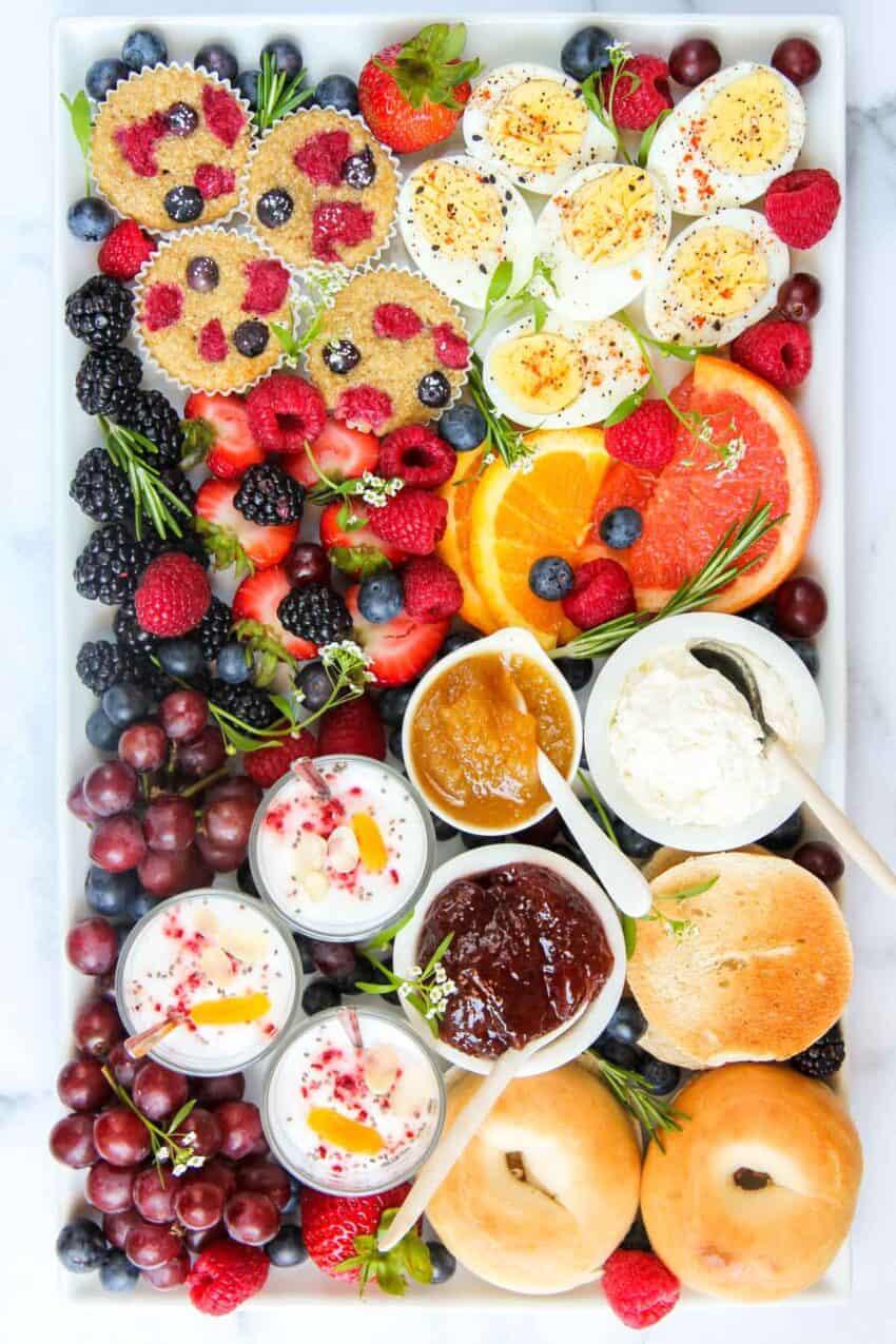 Breakfast Board with mini bagels, spreads, yogurt parfaits, mini muffins, eggs and fruits