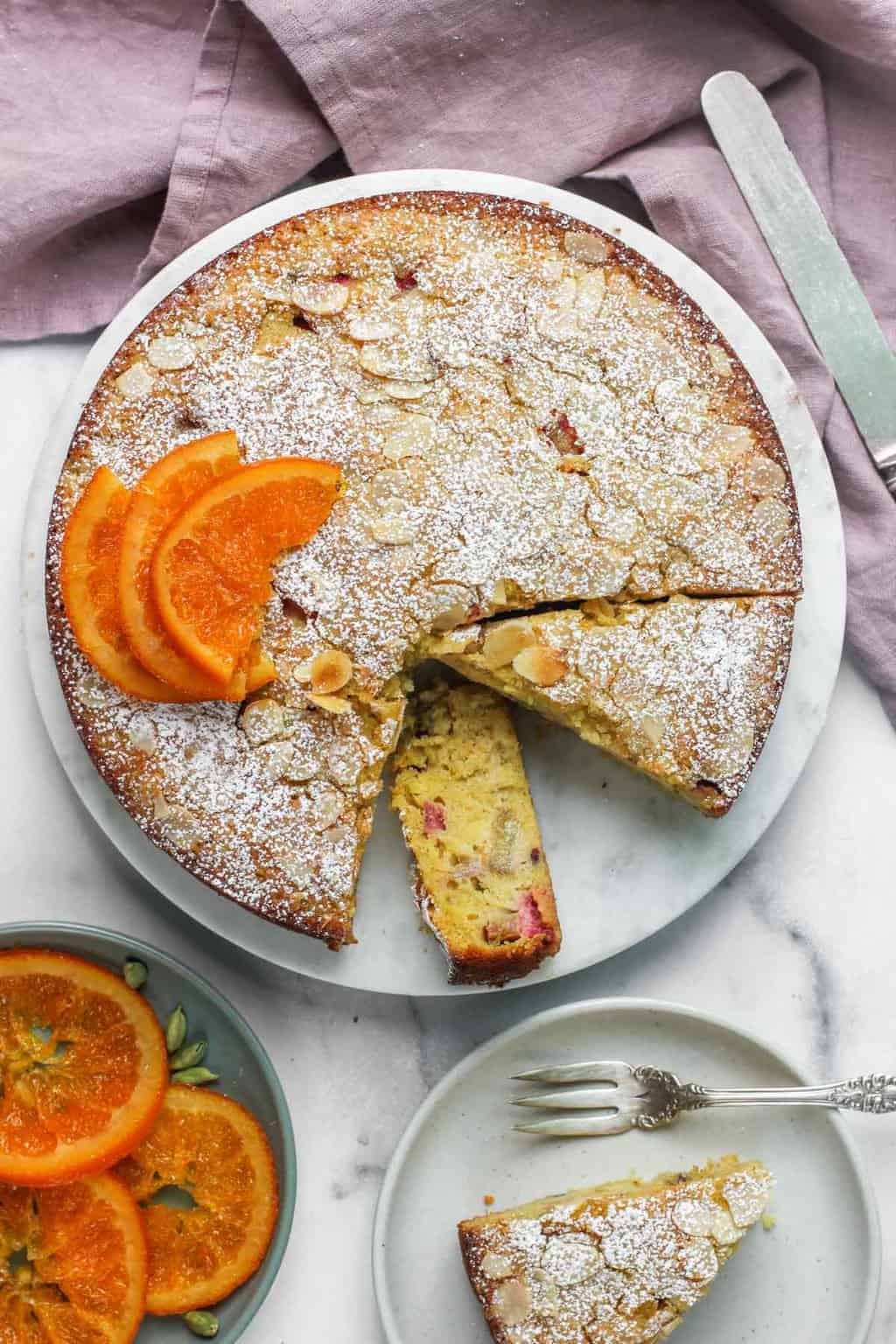 rhubarb almond cake with powdered sugar and candied orange slices