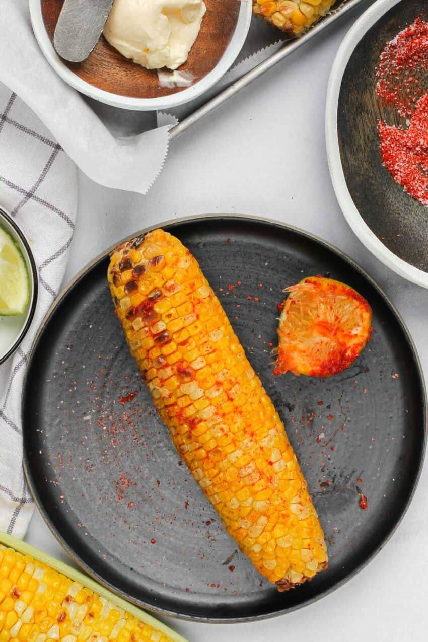 corn on the cob rubbed with salt, chili and lime on a black plate