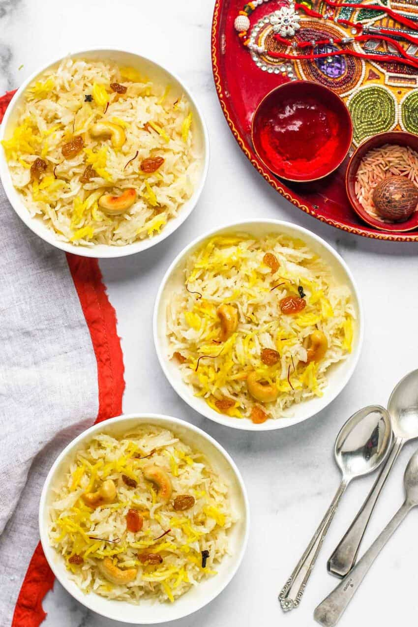 sweet coconut rice served in 3 white bowls with rakhi thali