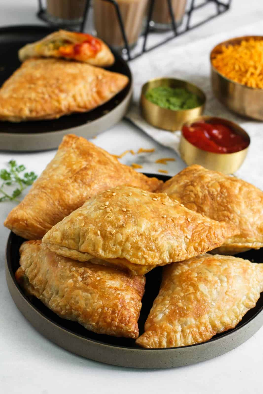 Jalapeno Cheese samosas in a black platter with chutney and ketchup on the side