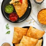 JAlapeno cheese samosas in 2 plates served with ketchup, chutney and chai