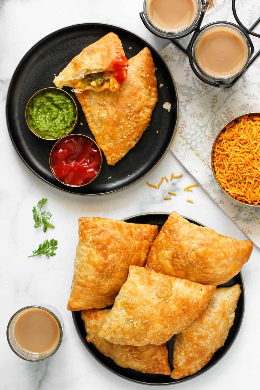 Jalapeno Cheese samosas in 2 plates served with chutney, ketchup and chai