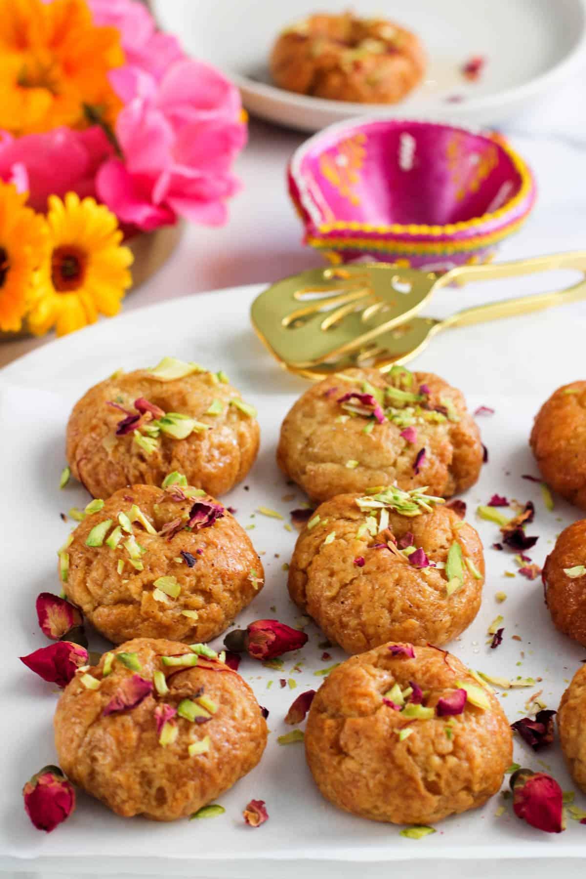 Balushahi garnished with pistachios and rose petals